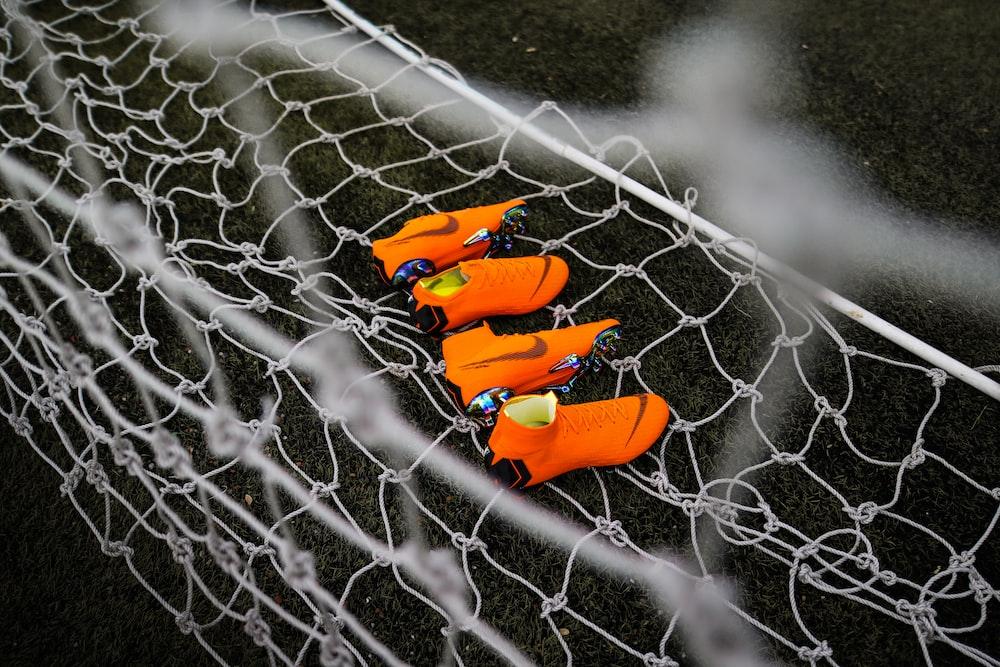 two pairs of orange Nike cleats on goalie