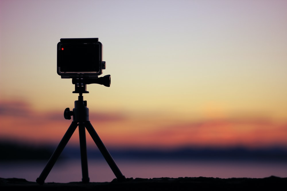 selective focus photo of black action camera on black tripod