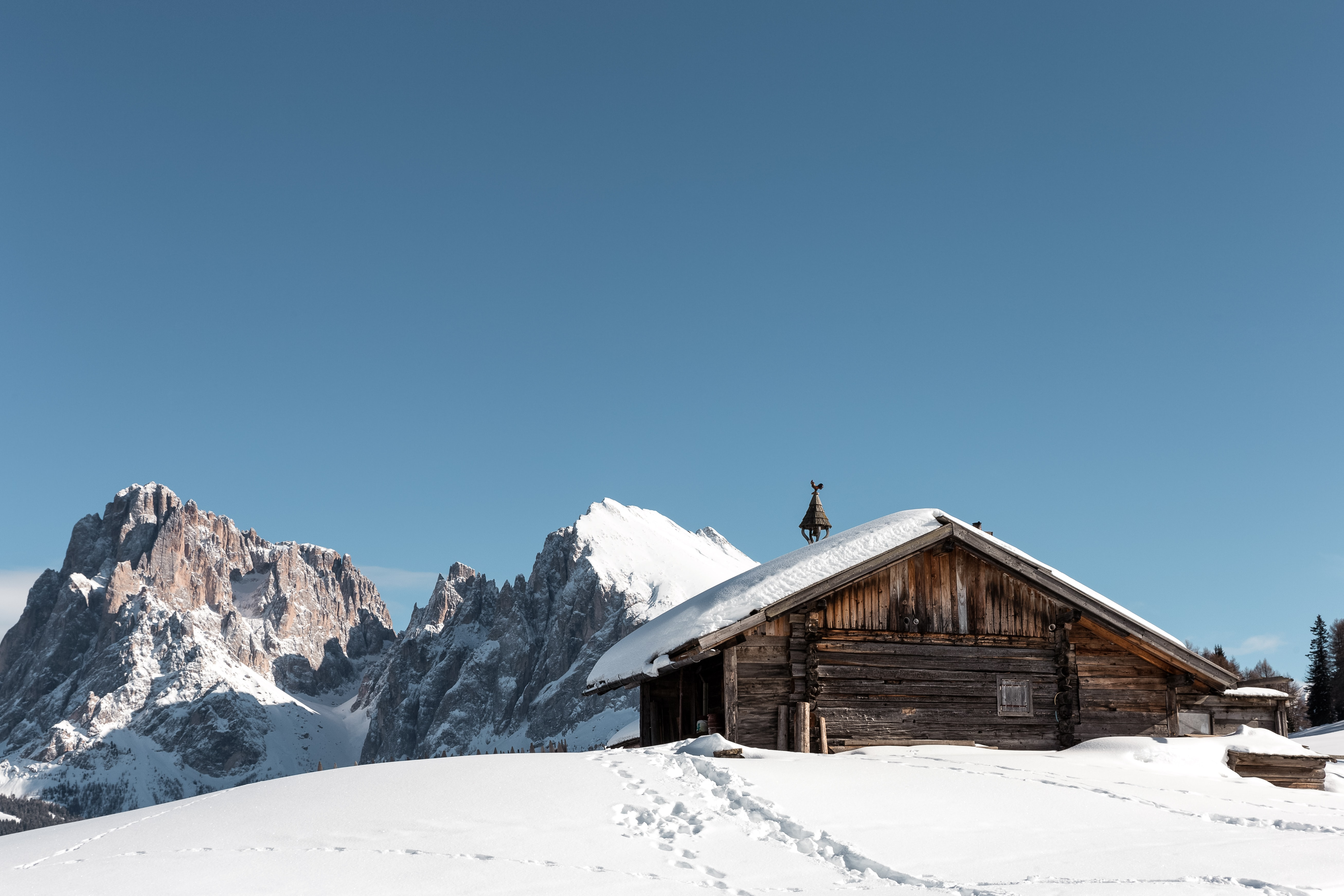 brown wooden house within mountain range during daytime