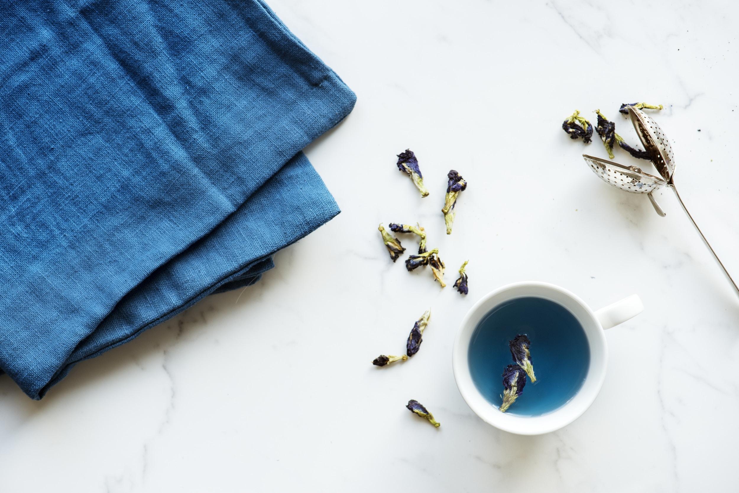 white ceramic mug beside blue textile