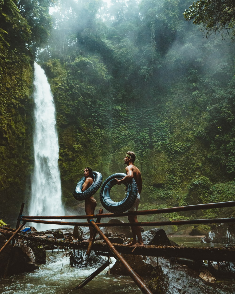 photo of man and woman holding tires and walking on bridge near waterfalls
