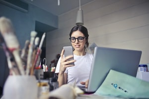 Woman at a desk looking at an iPhone
