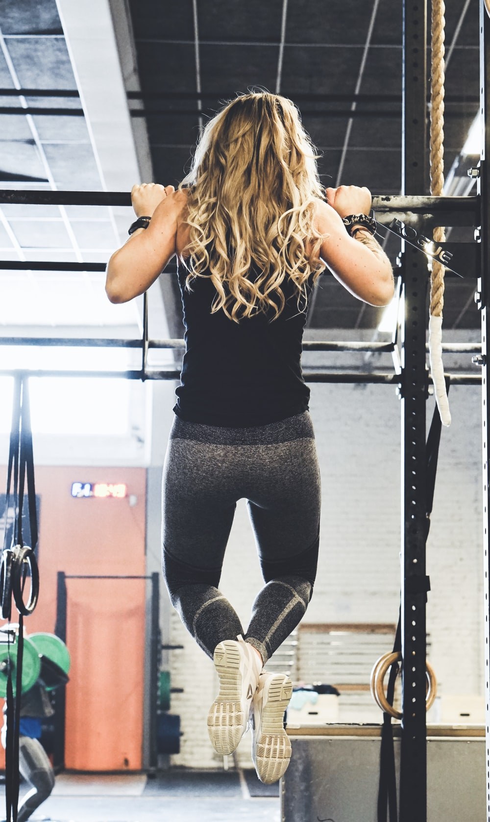 woman working out using black power rack