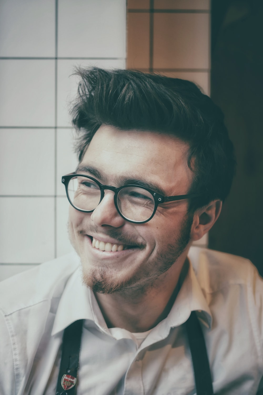 photo of man wearing black-framed eyeglasses beside wall tile