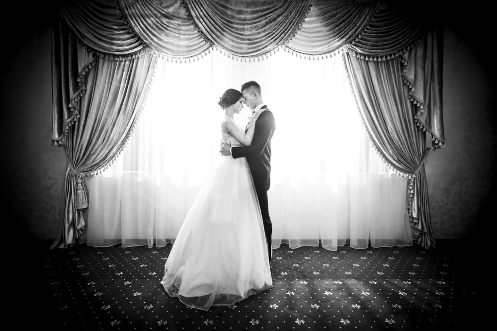 grayscale photography of couple facing in front curtain