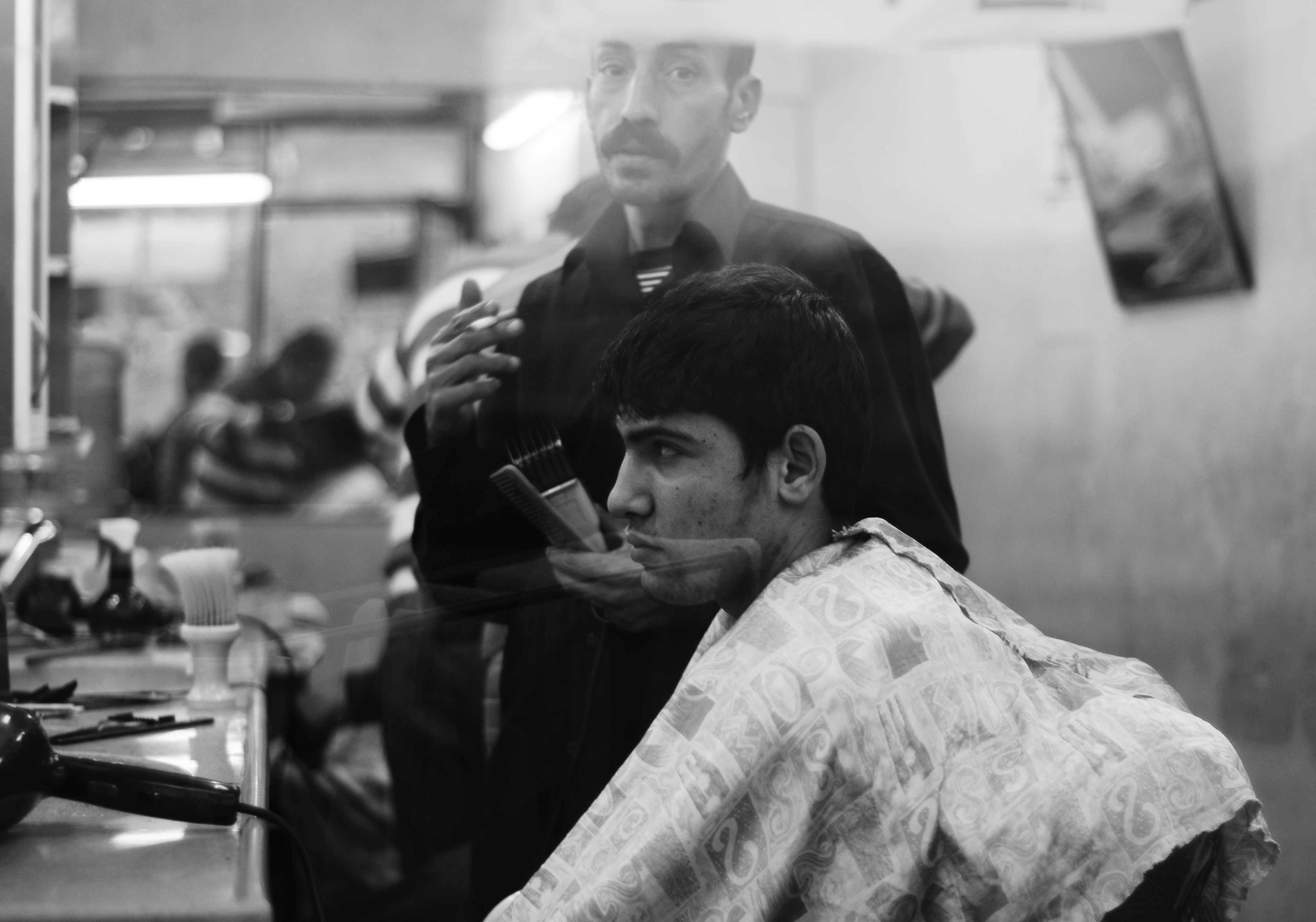 grayscale photo of man inside barber shop