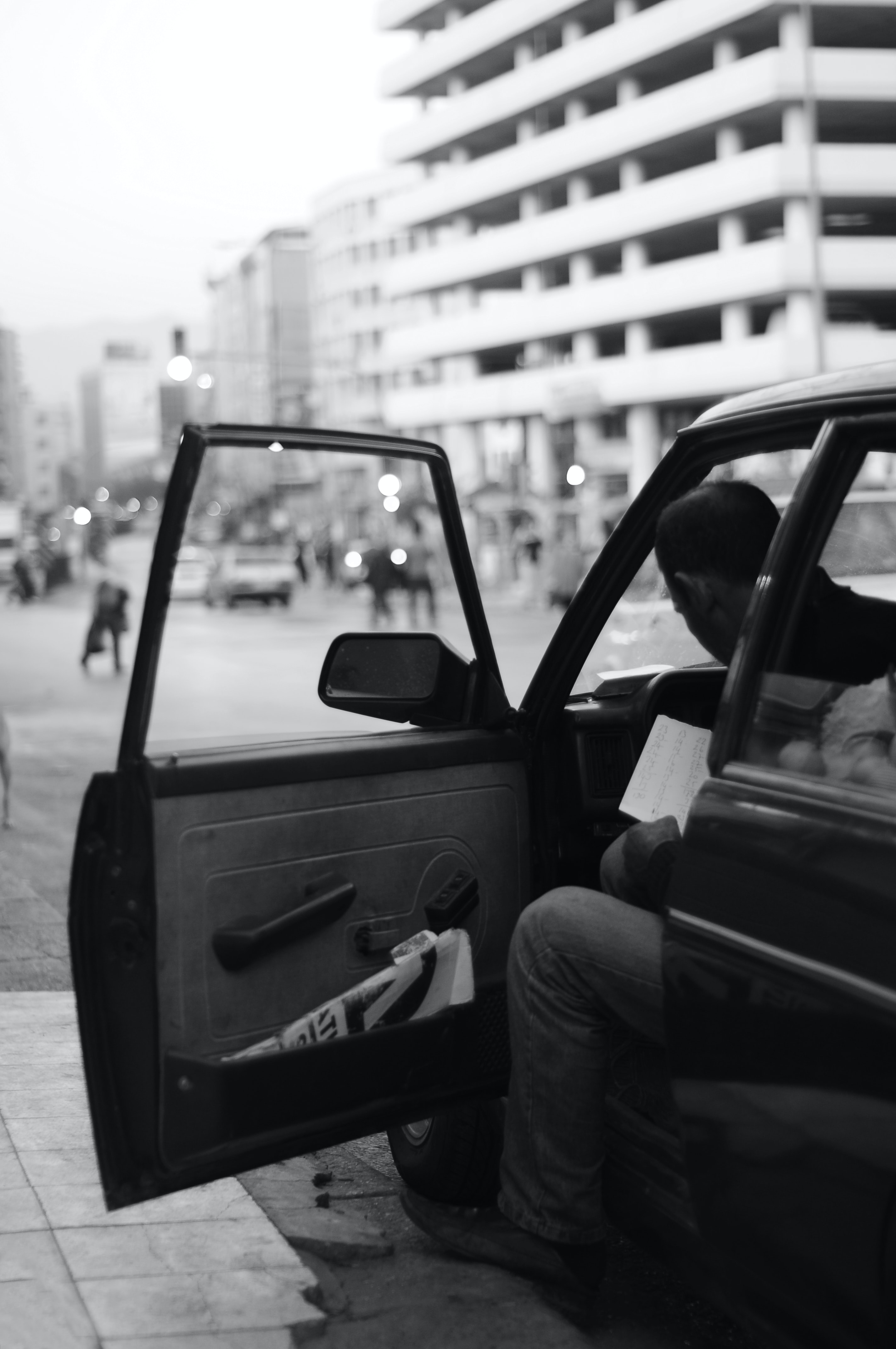 grayscale photography of man sitting inside car while door open