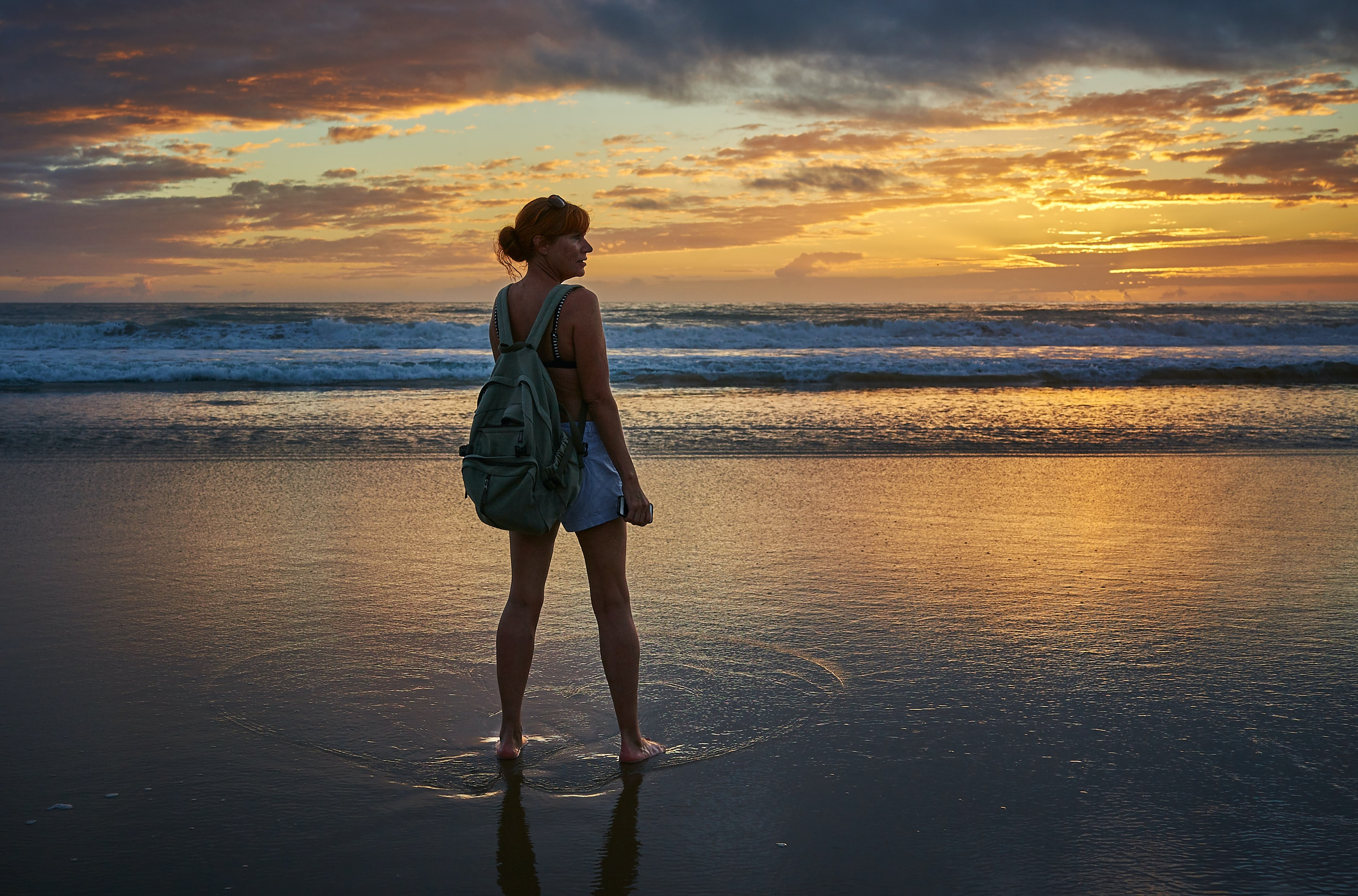 woman standing near the seashore during golden hour