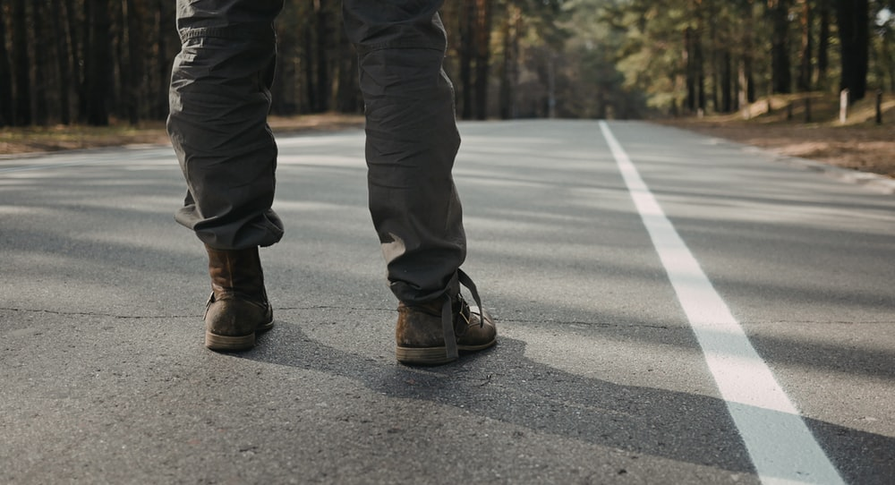 person standing in middle of concrete road near trees