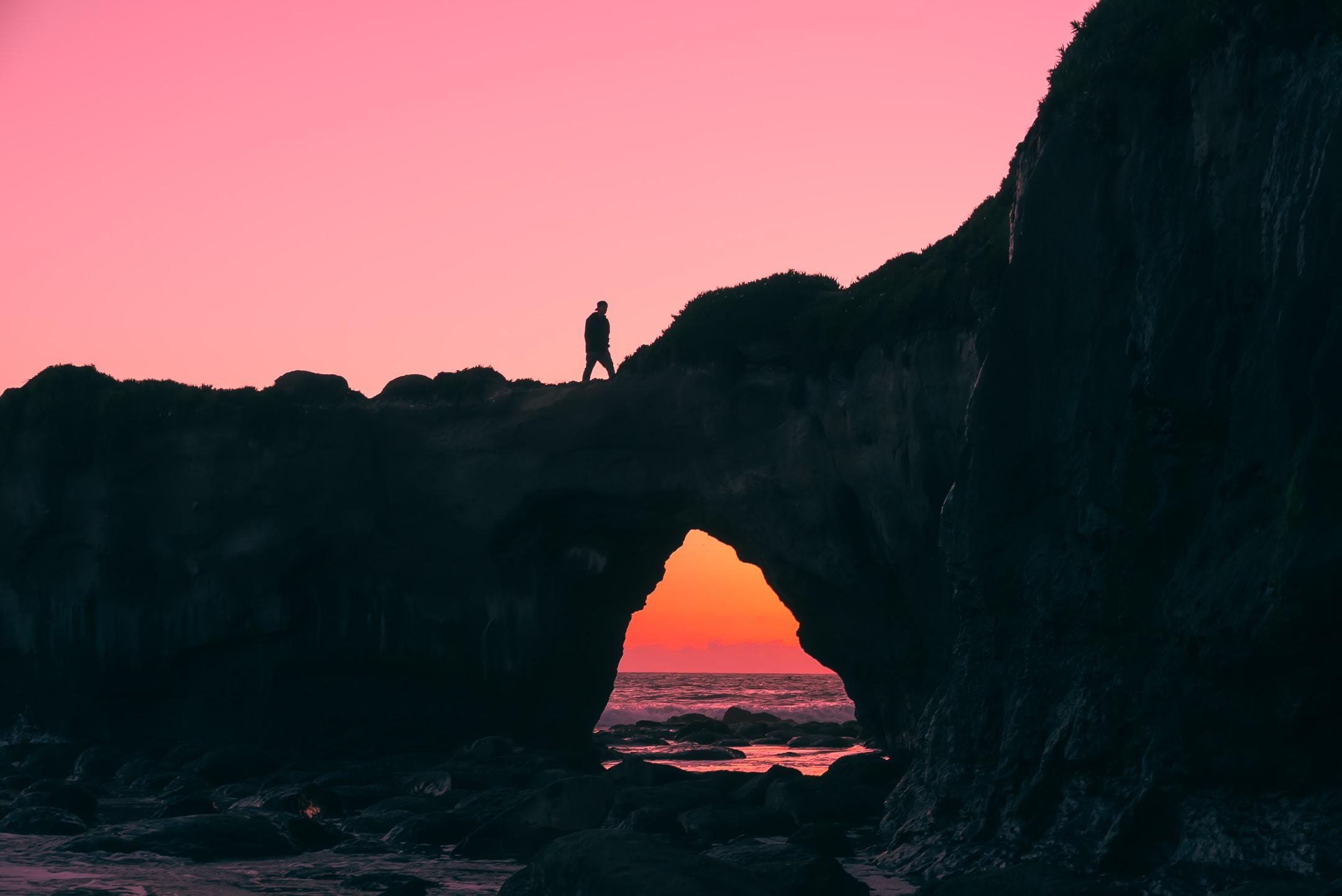 silhouette of man walking on top of large rock