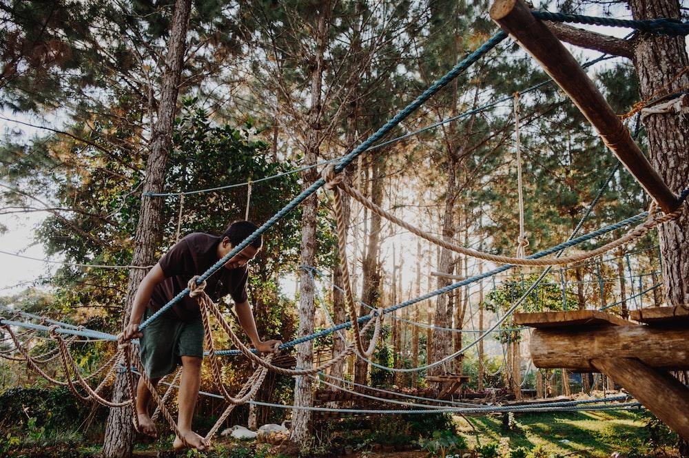 photo of man walking on rope tree