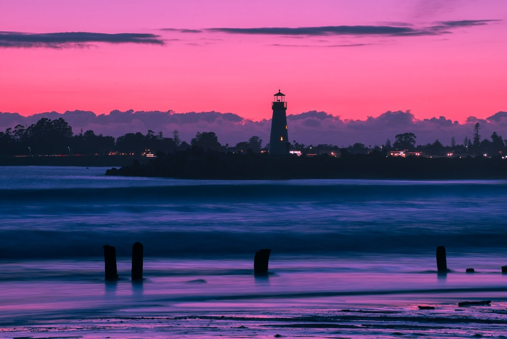 silhouette photo of lighthouse during golden hour