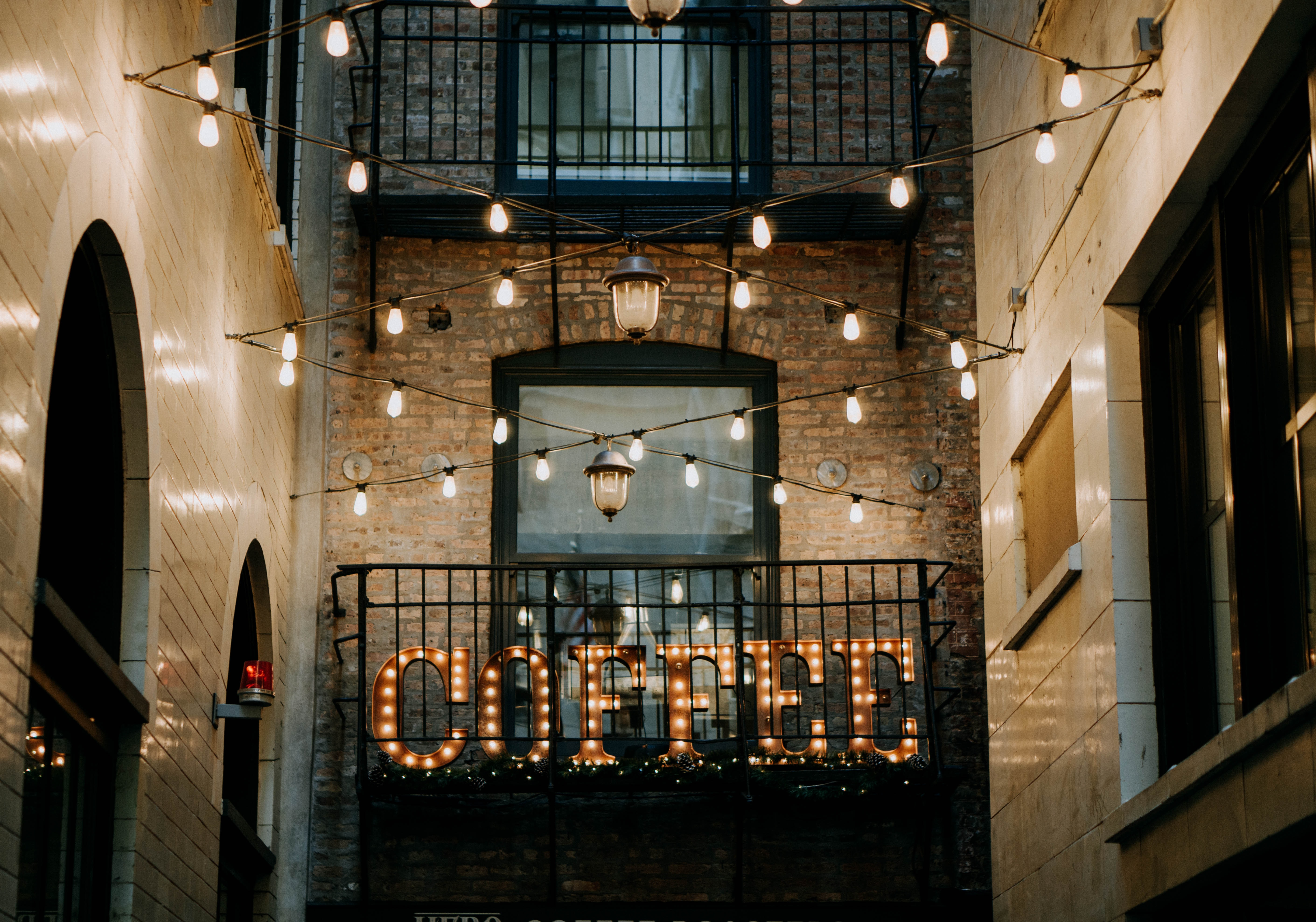 brown Coffee LED signage between buildings