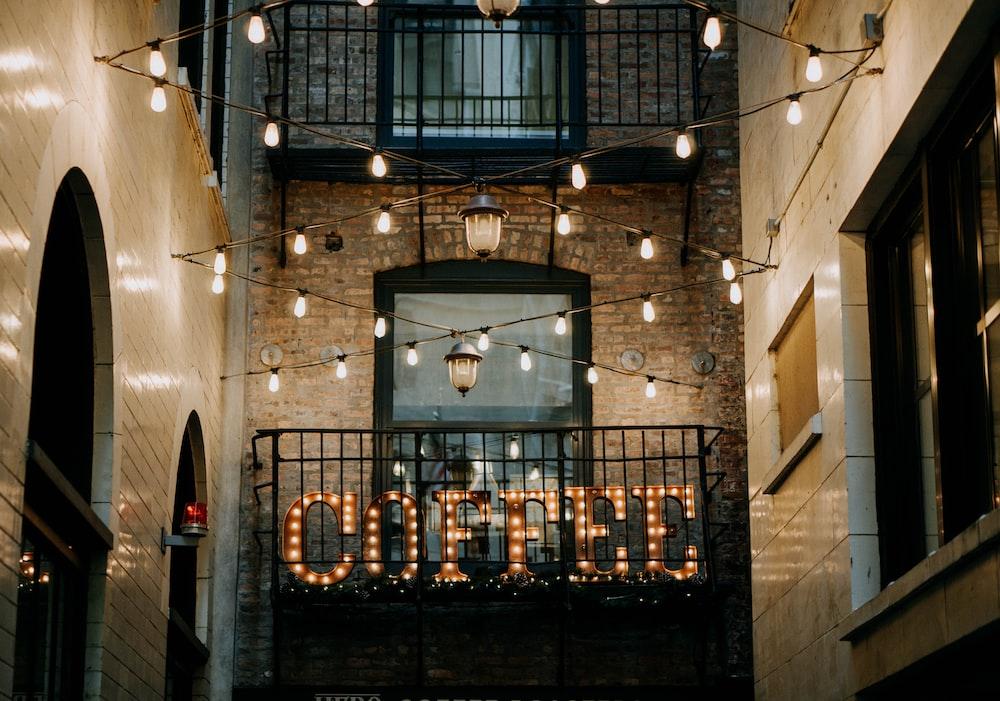 brown Coffee LED signage between buildings