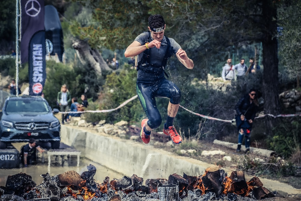 man jumping on flaming charcoal
