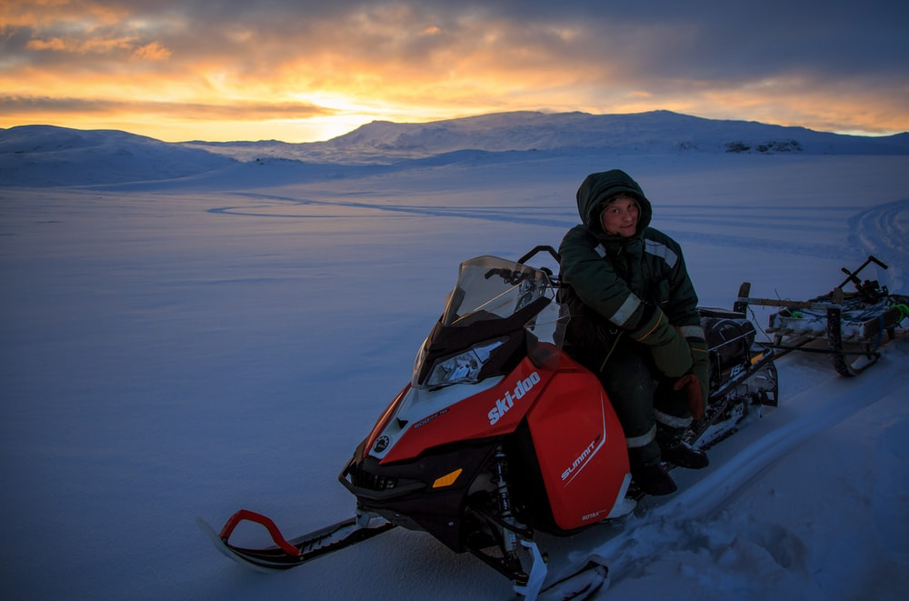 person sitting on snowmobile