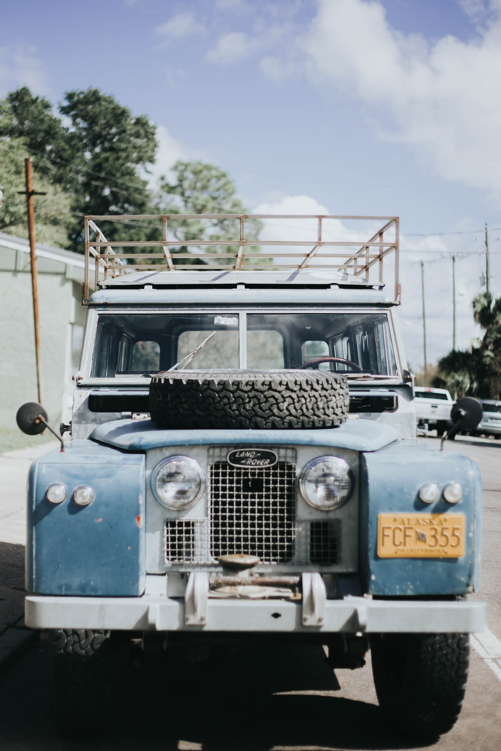 photography of blue vehicle parked on road