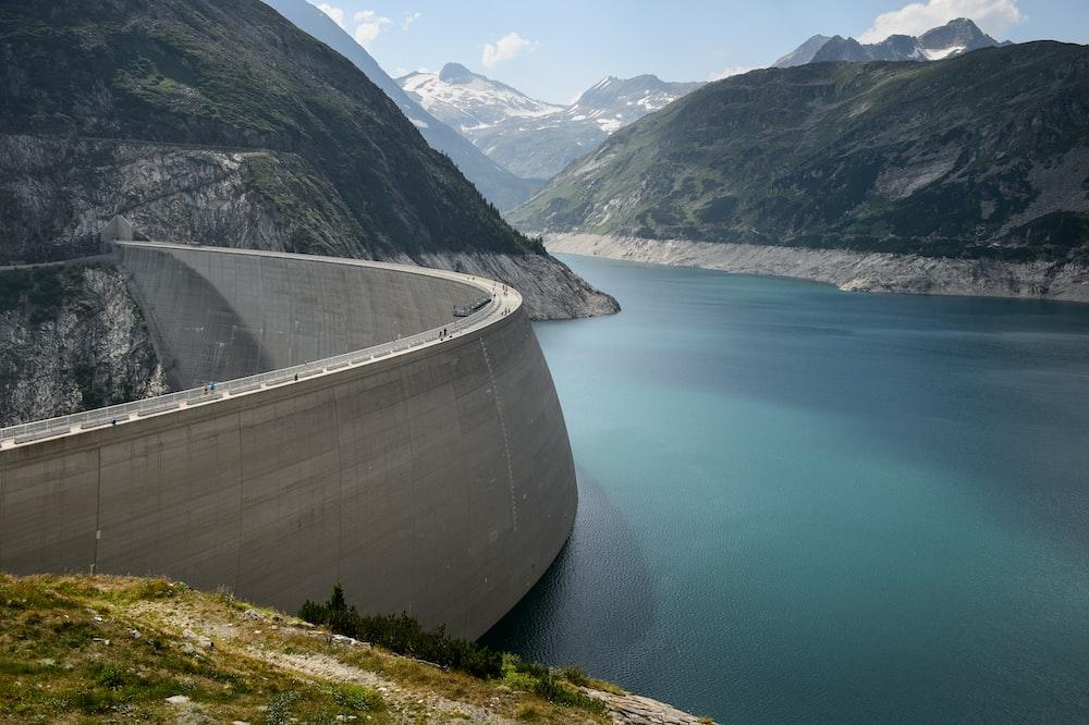 photo of concrete dam in lake near mountains during daytime