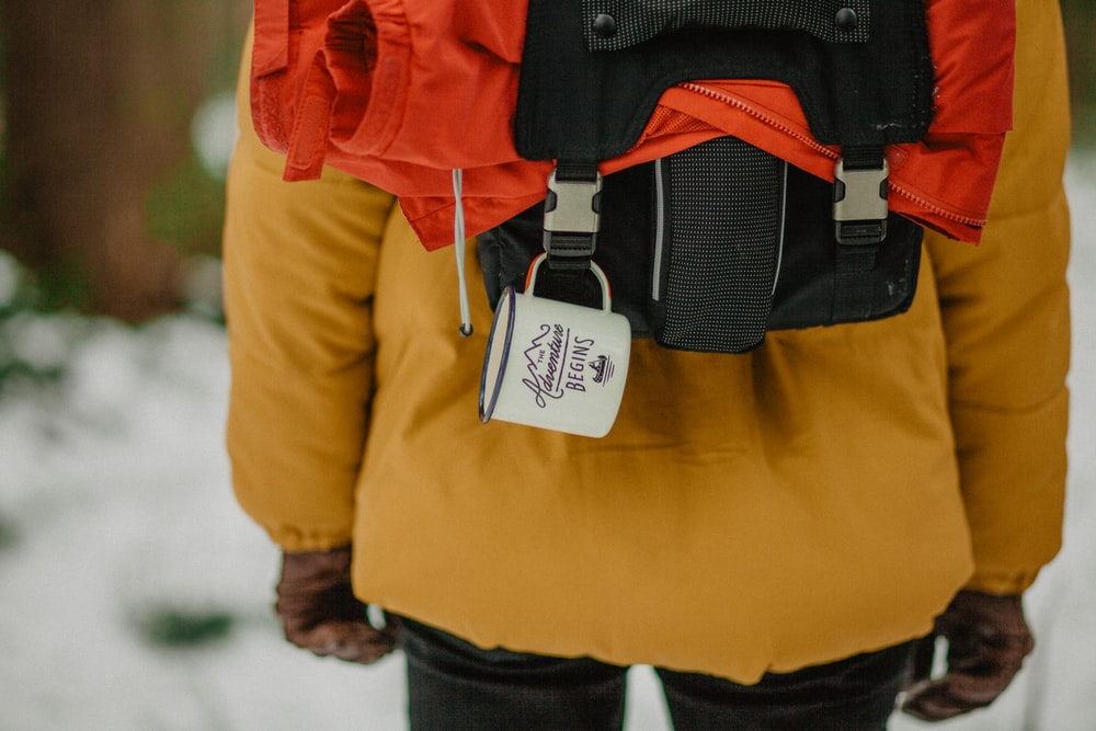 selective focus photograph of person wearing orange coat and black backpack