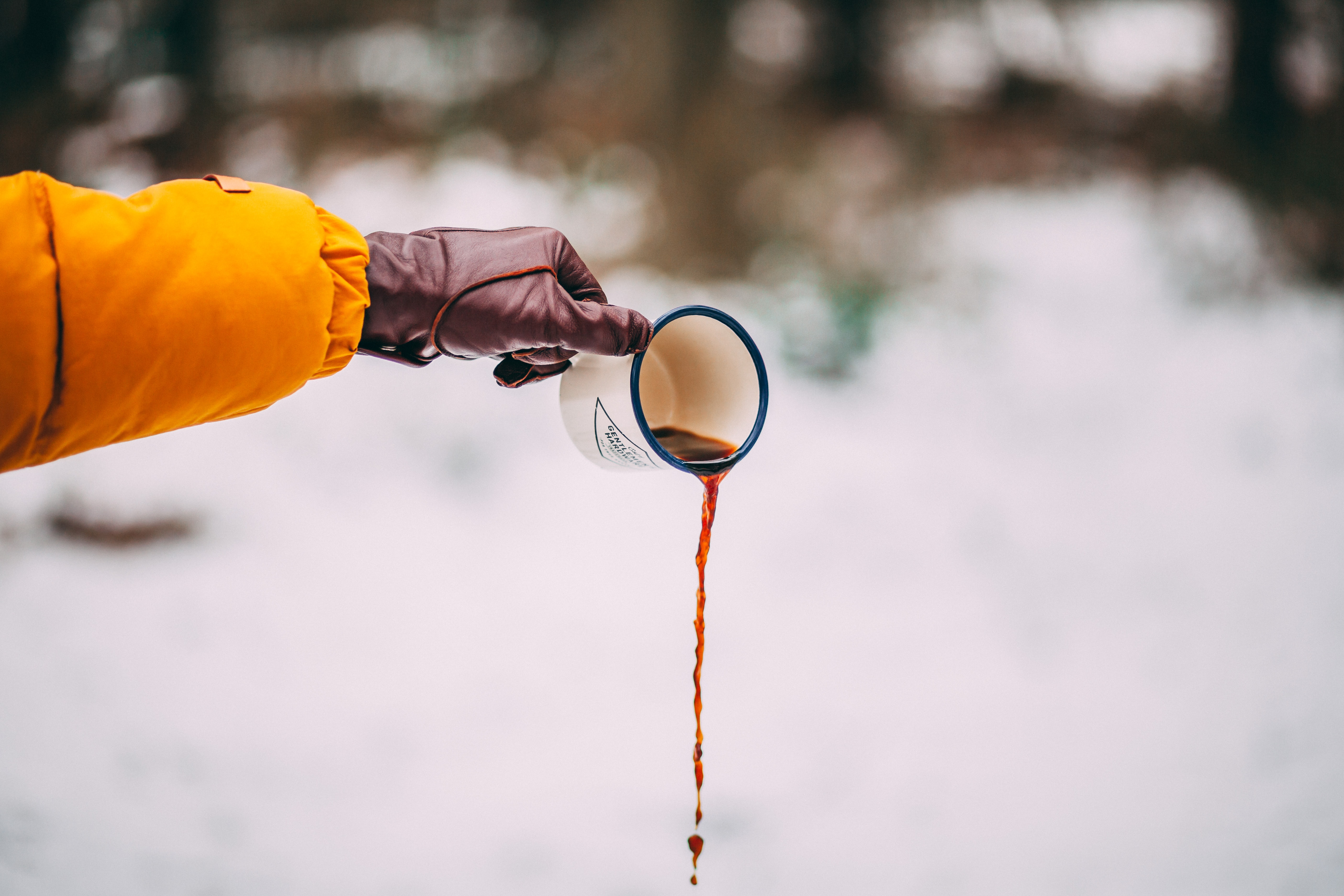 person pouring out coffee from white ceramic cup