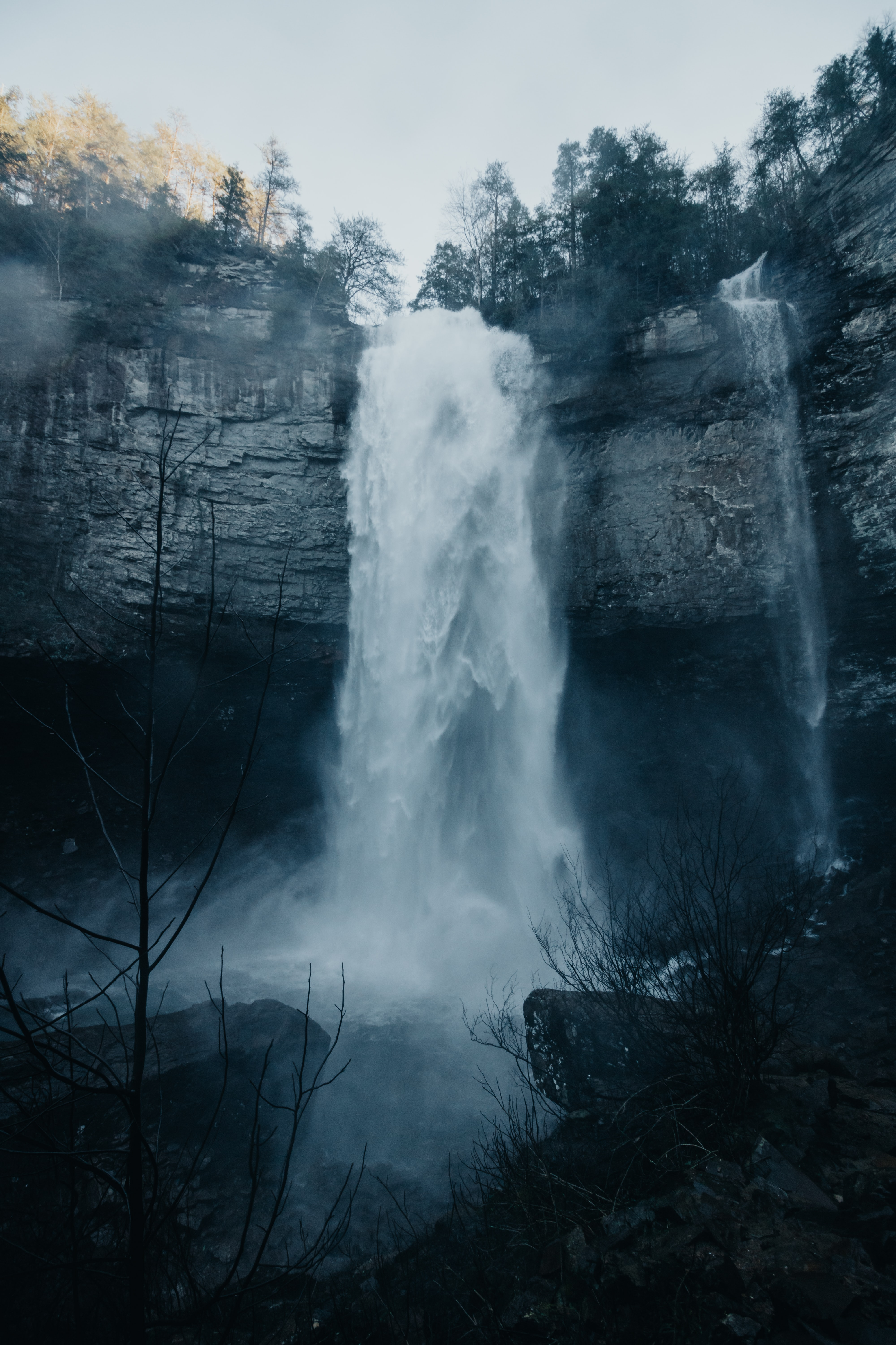time-lapse photography of waterfalls under white clouds
