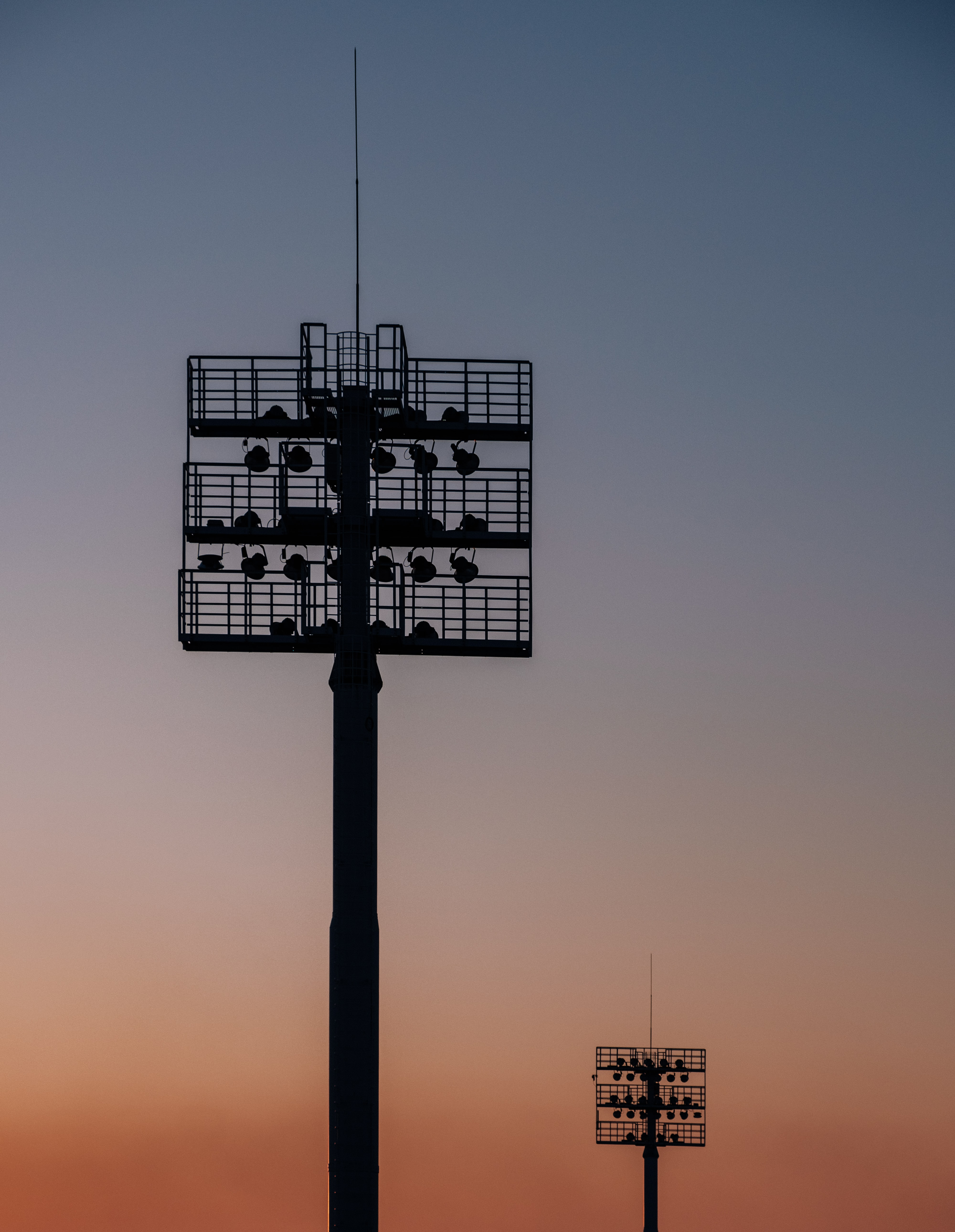 silhouette of two spot light tower