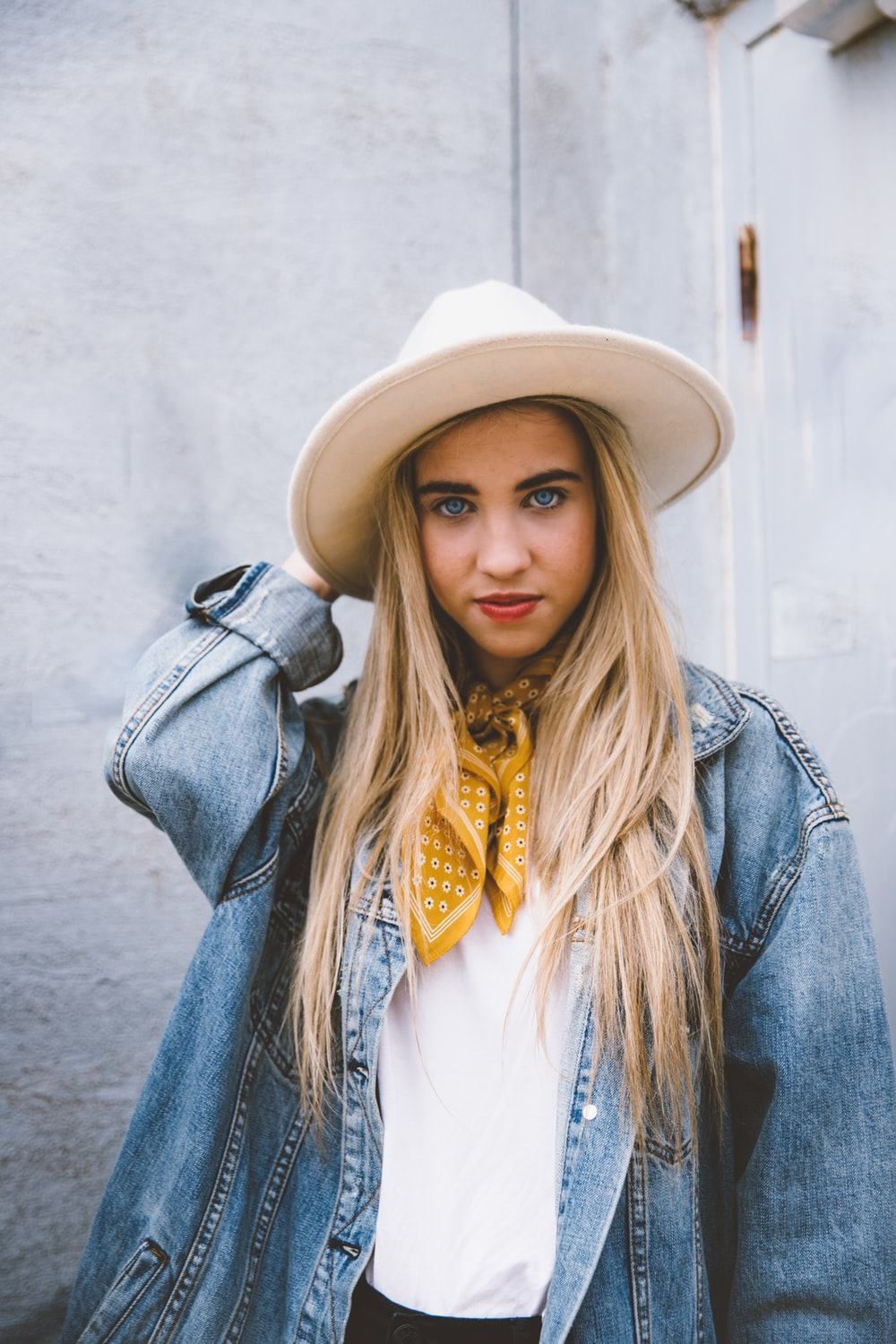 woman wearing blue denim jacket and white hat