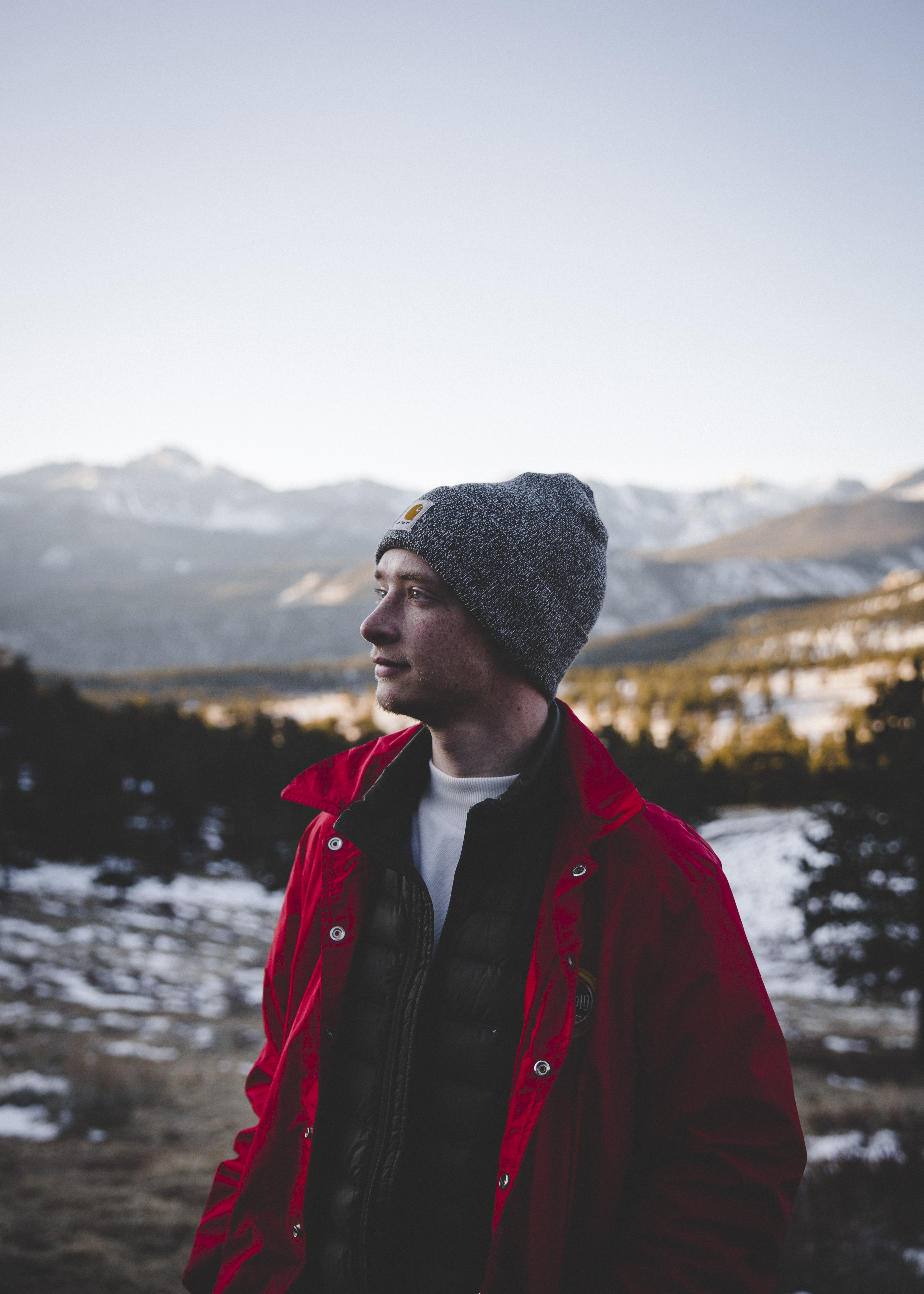 man in gray knit cap with mountain background