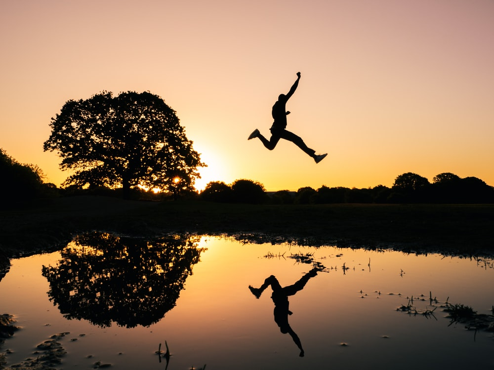 silhouette photo of man jumping on body of water during golden hour