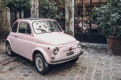 pink fiat 500 on gray concrete floor rosa parks teams background