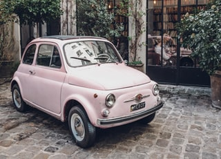 pink FIAT 500 on gray concrete floor