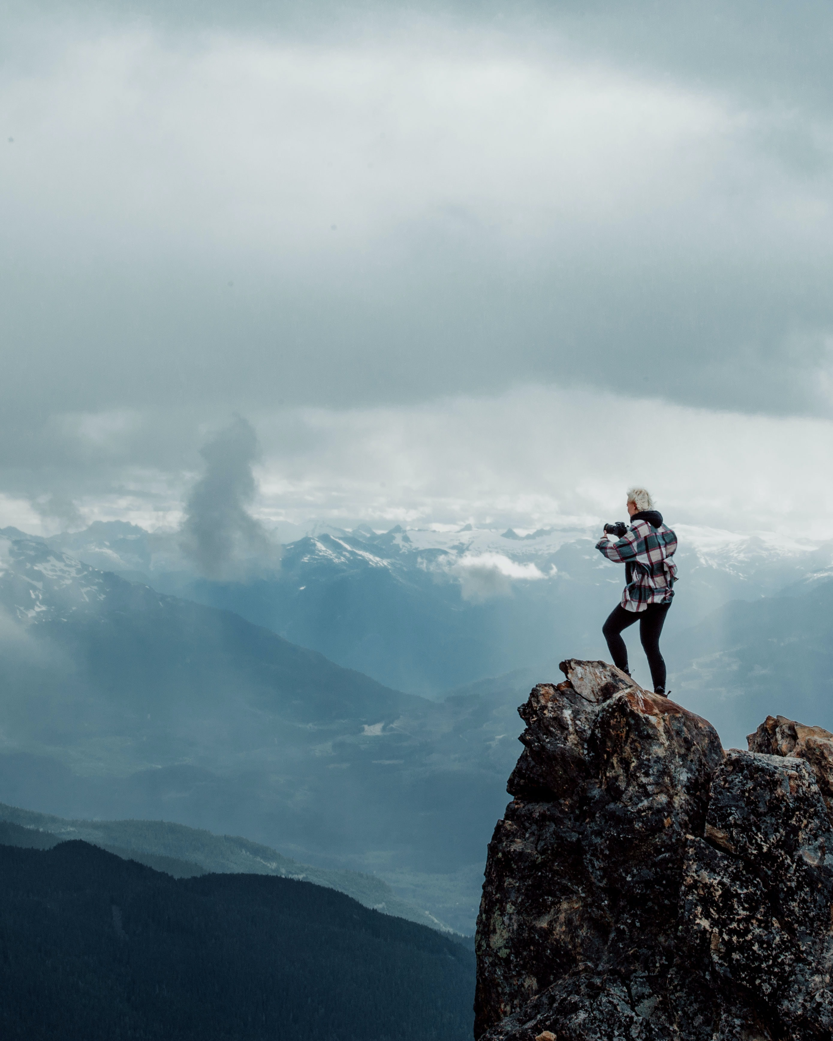 person standing on top of rock mountain during daytime