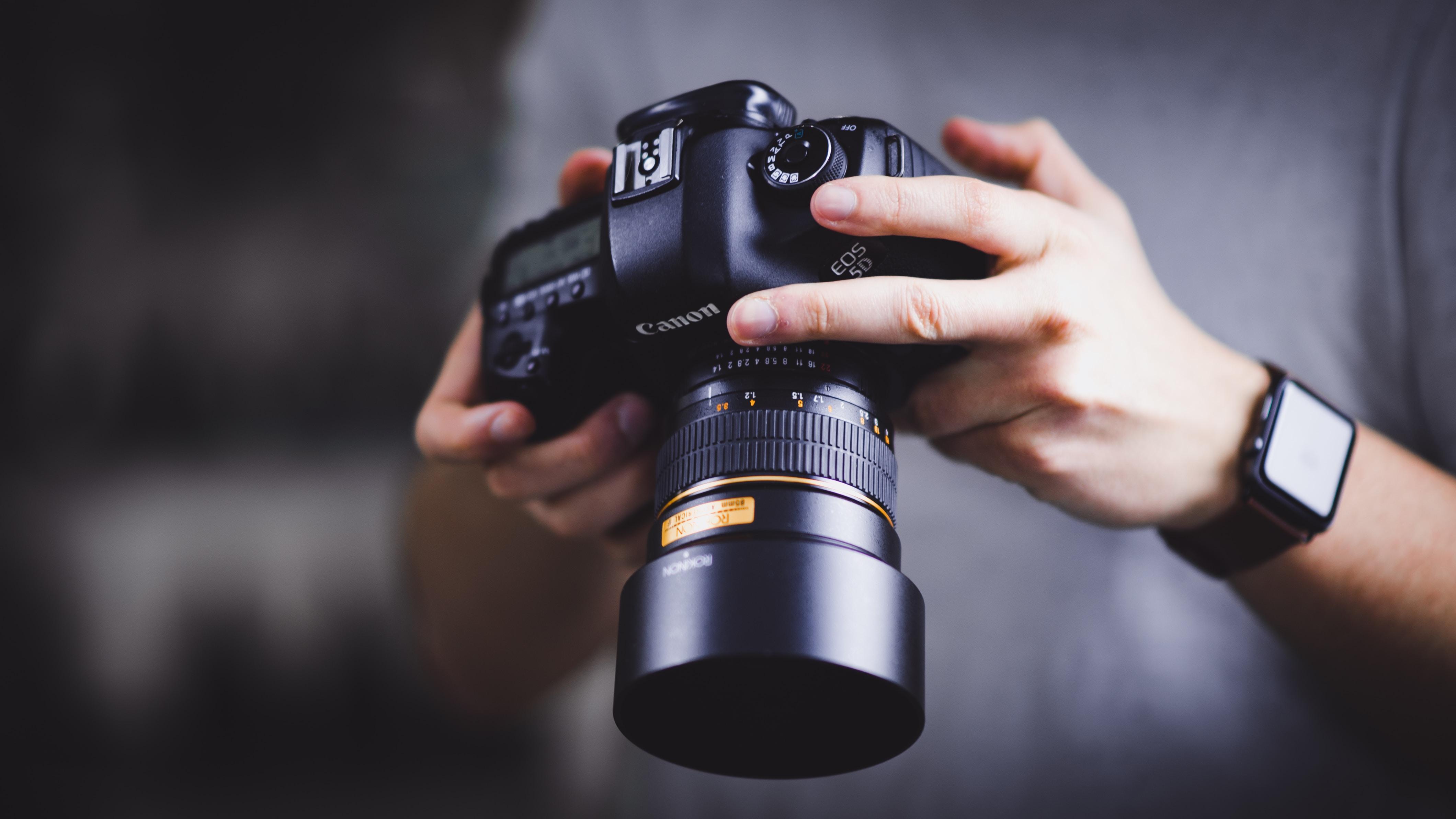 person holding Canon DSLR camera