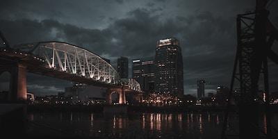 white and black bridge near high rise building at nighttime