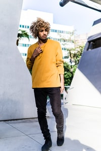 man in yellow long-sleeved V-neck shirt standing near white wall during daytime