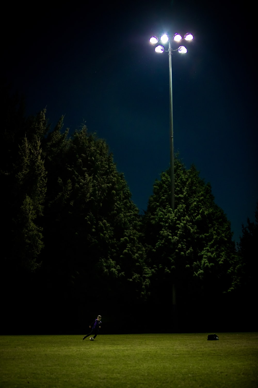man playing football during nighttime