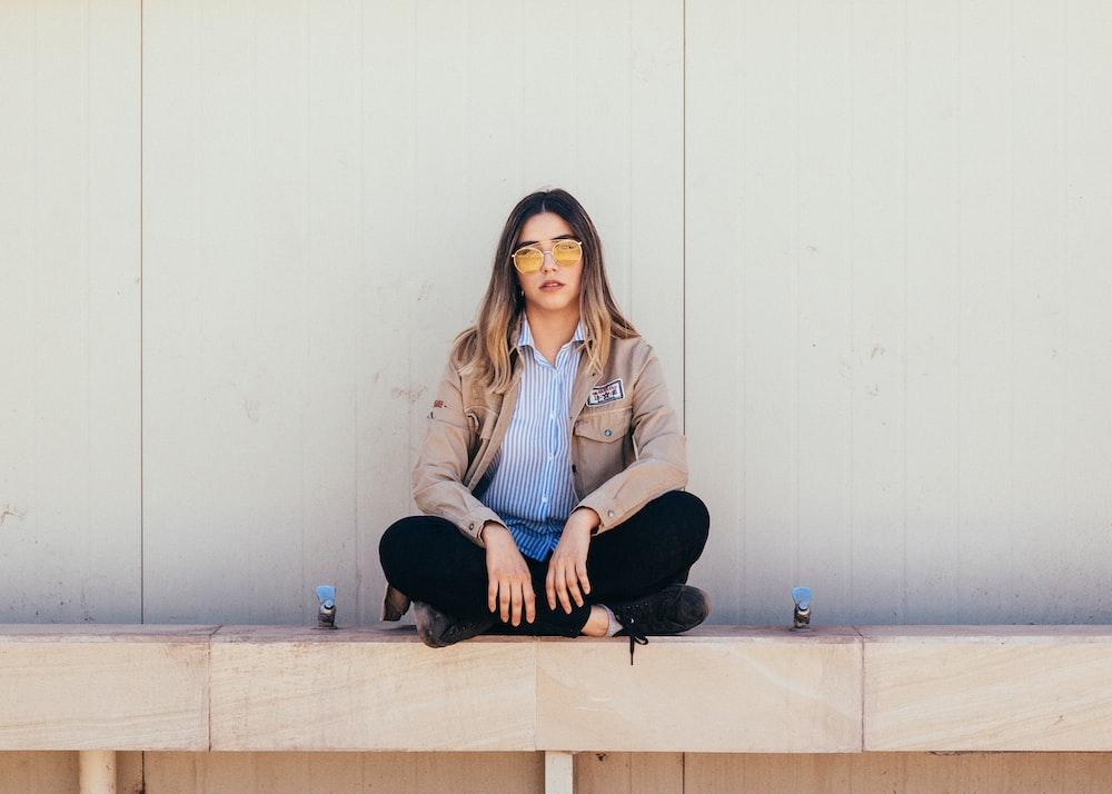 woman sitting on white concrete flooring