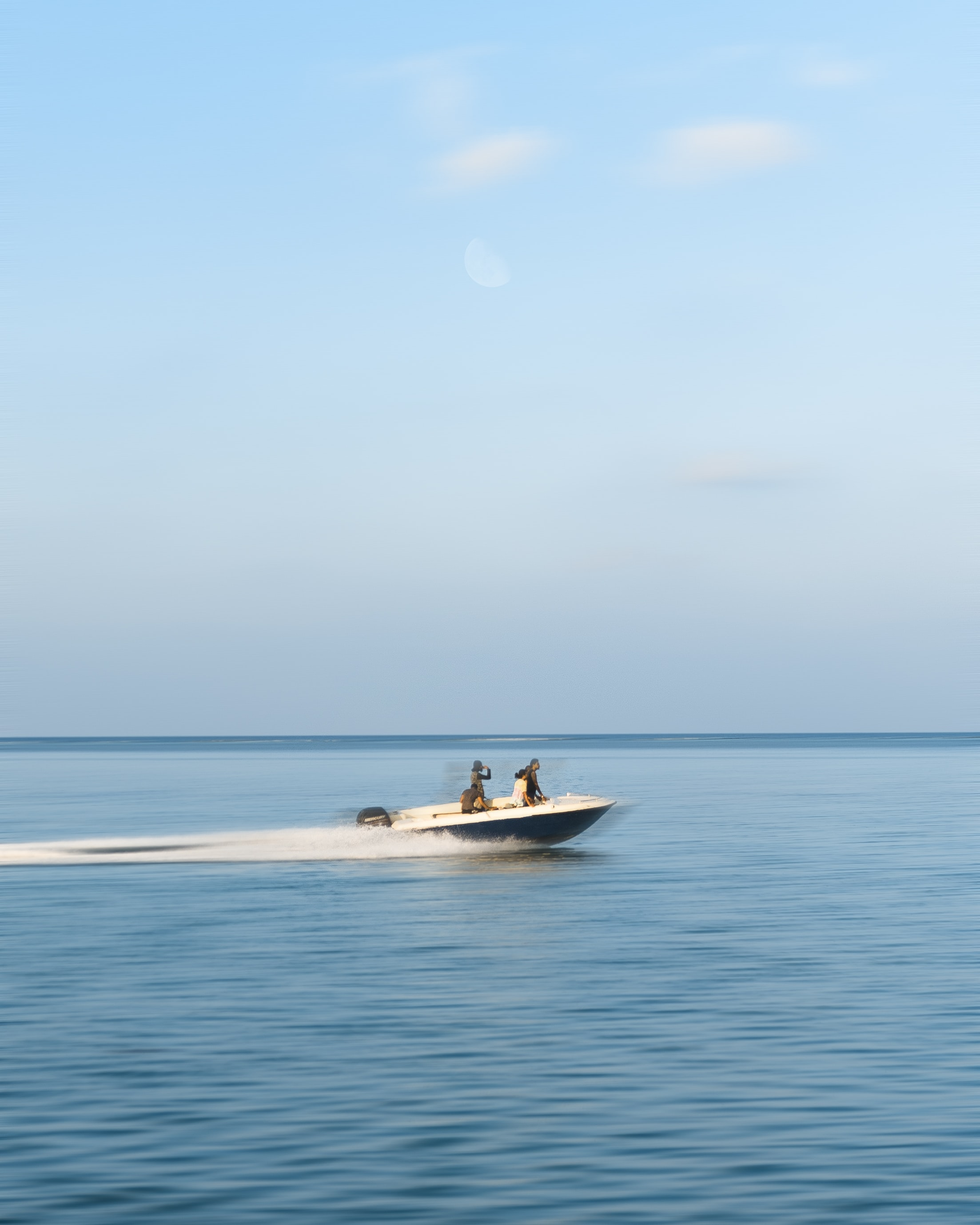 three person riding on motorboat under white clouds at daytime