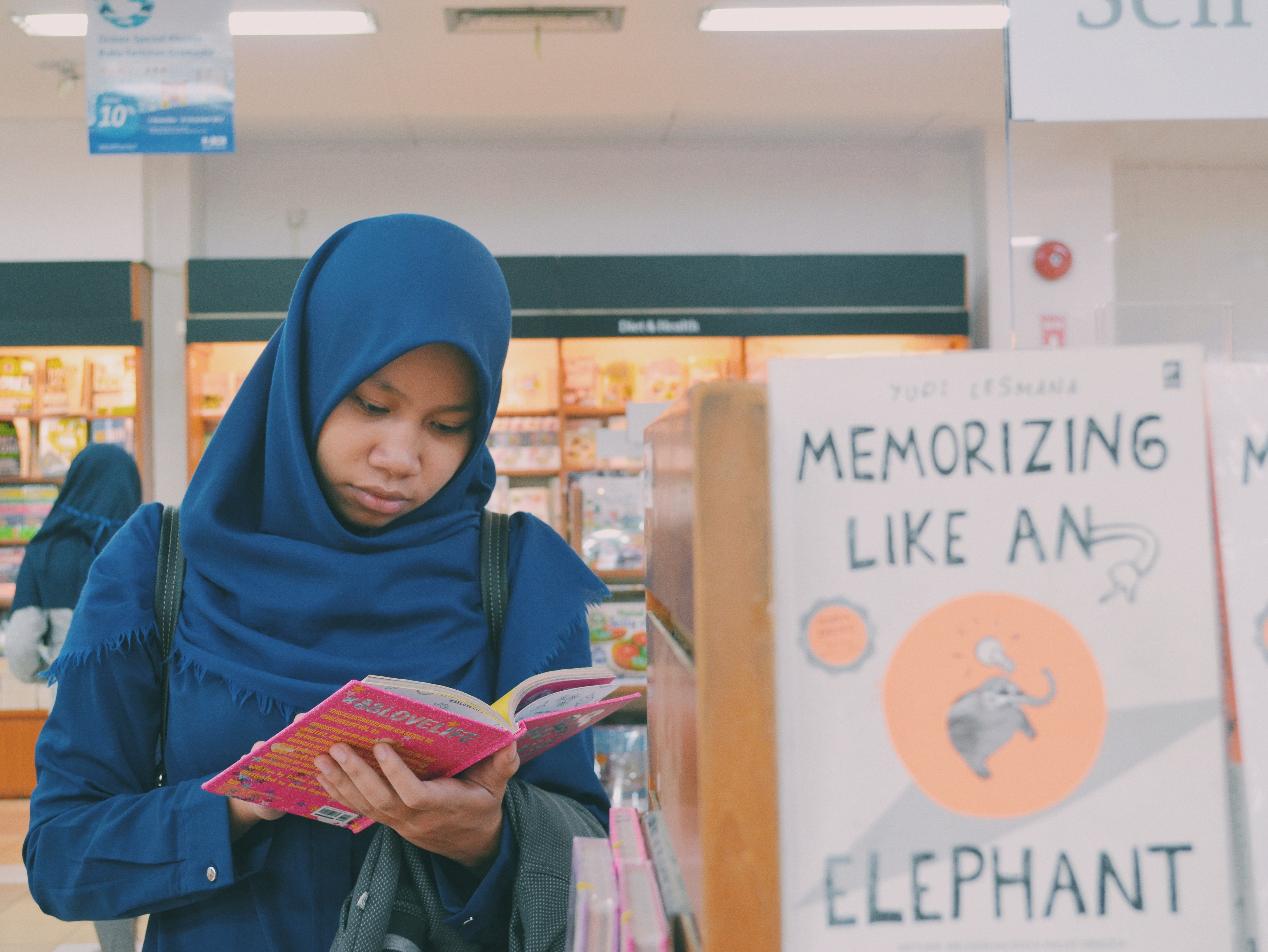 woman reading book inside book store