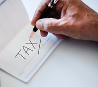 person writing tax on white printer paper
