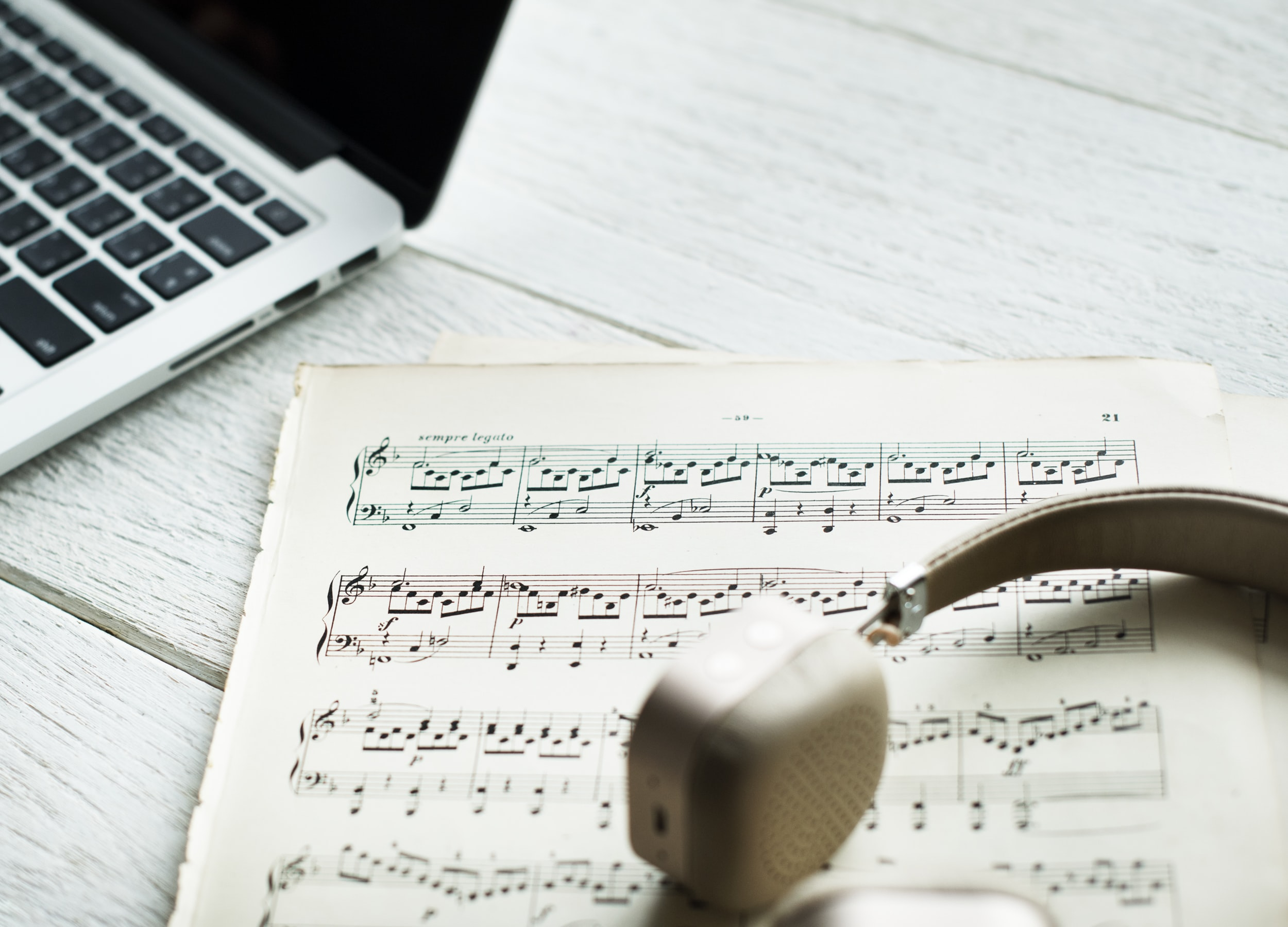 headphones on top of musical composition note beside laptop