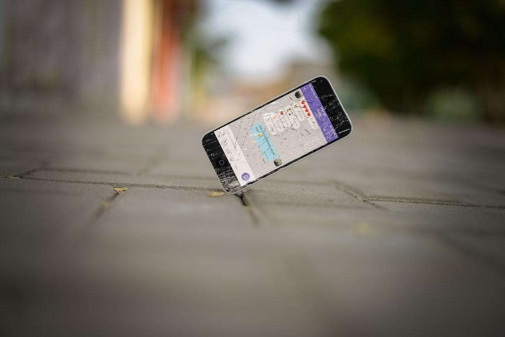 selective focus photo of iPhone balance on brick pavement