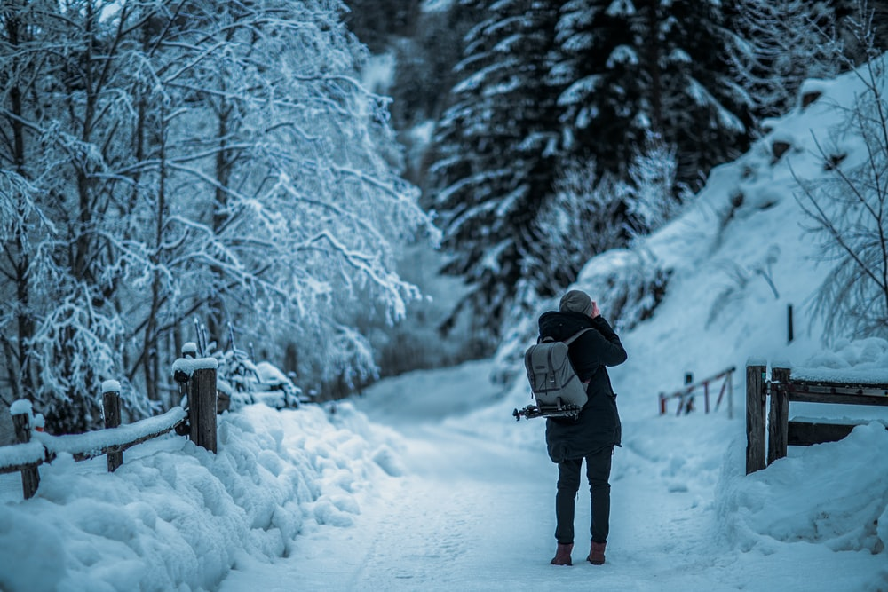 man standing in middle of snowfield during daytime