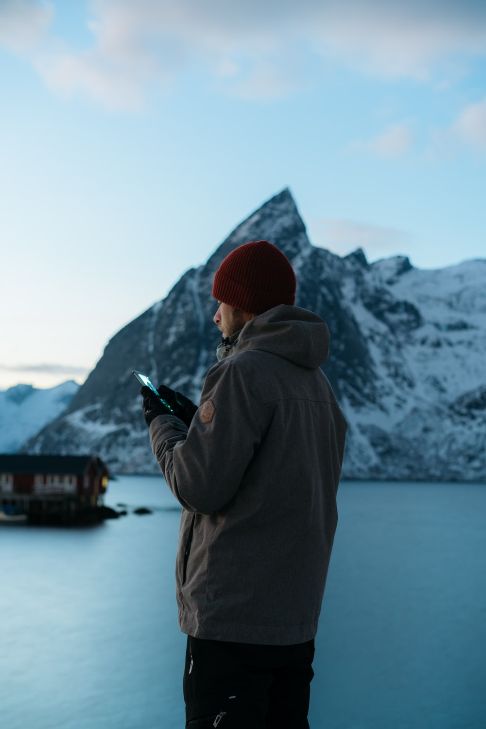 man using smartphone near mountain covered with snow