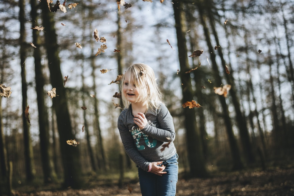girl in gray long-sleeved top running surrounded with trees