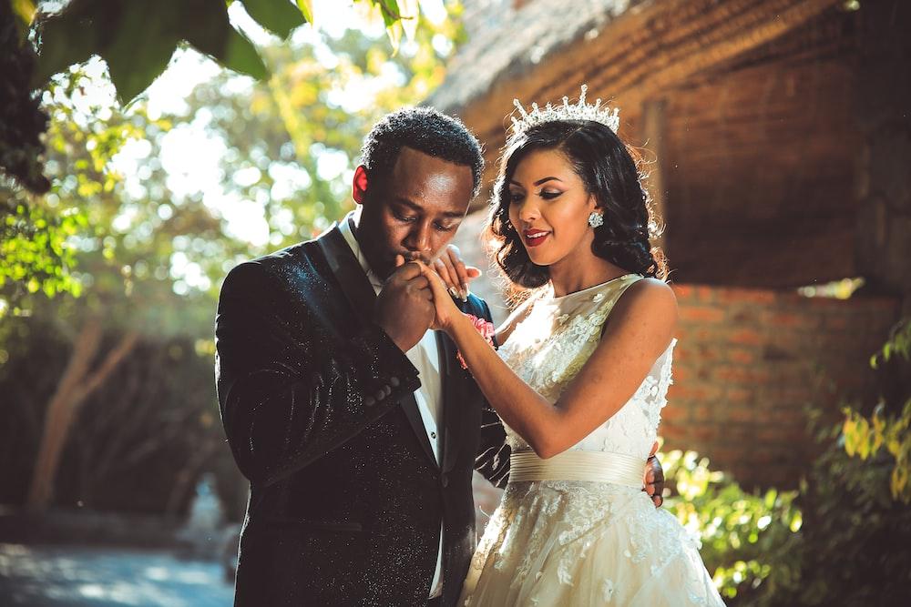 groom kissing bride's hand