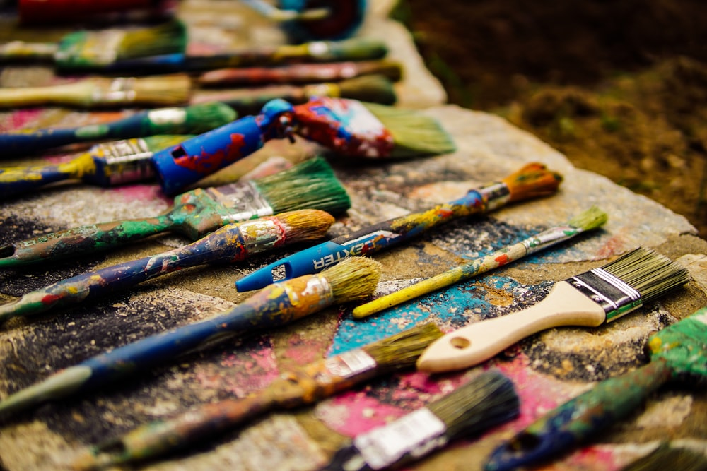 a lot of paint brushes on ground