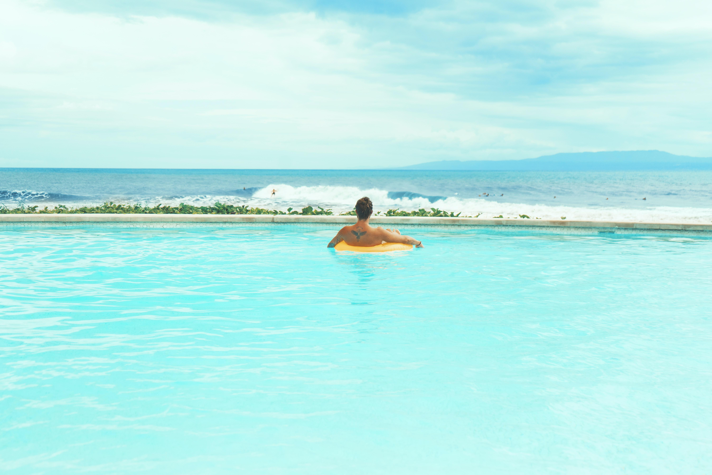 man swimming in pool during daytime
