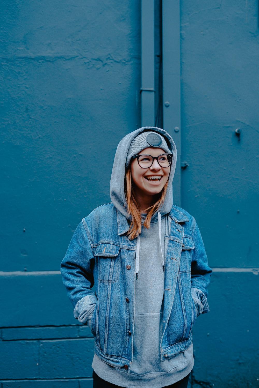 woman in blue jacket standing beside walls