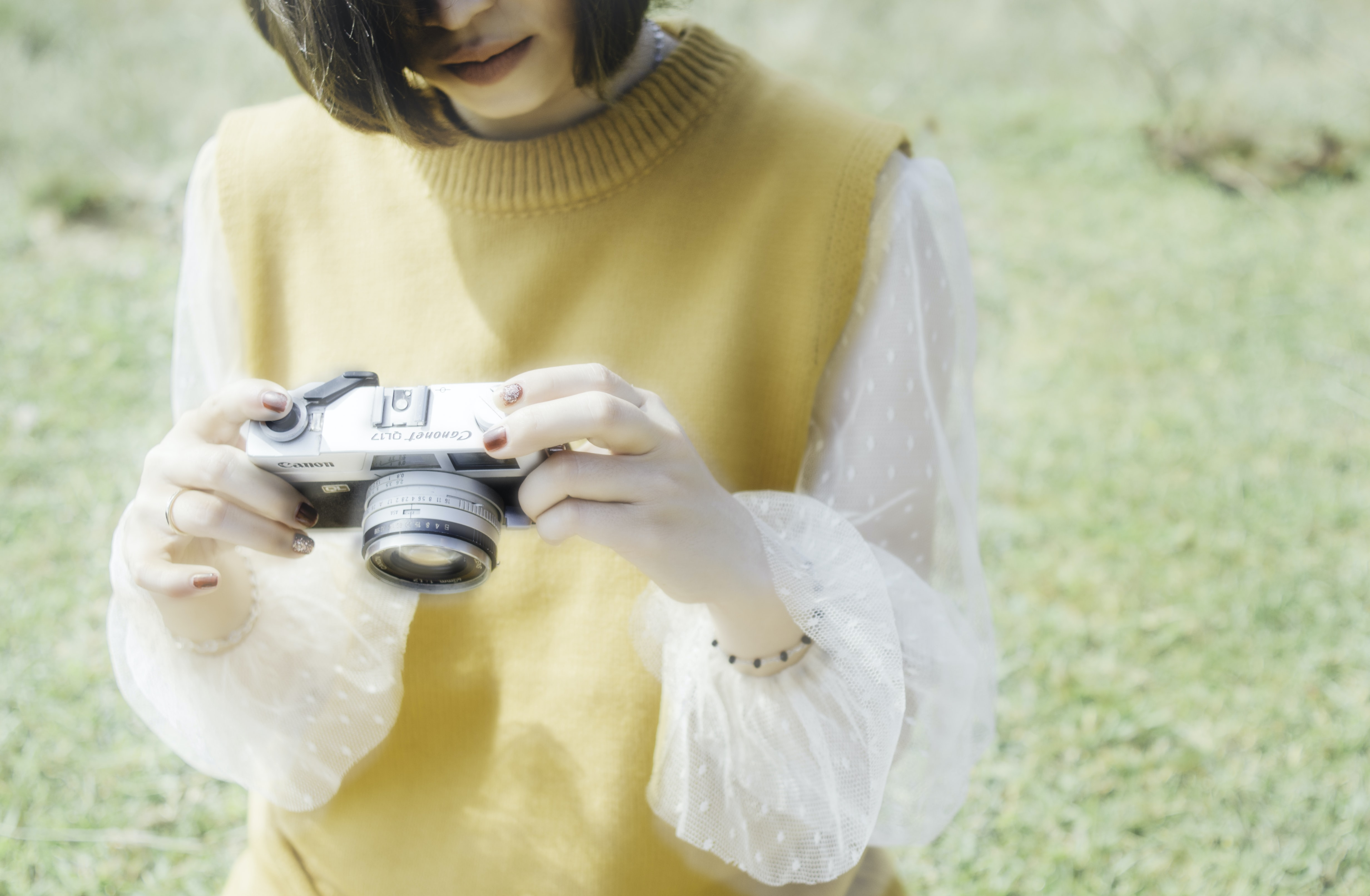 photo of woman holding and looking gray camera